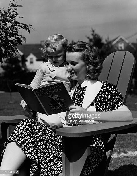 mother and daughter sitting on chair reading book - {{ contactusnotification.cta }} stockfoto's en -beelden