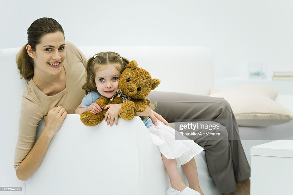 Mother and daughter sitting on couch, woman smiling at camera, girl holding teddy bear : Stock Photo