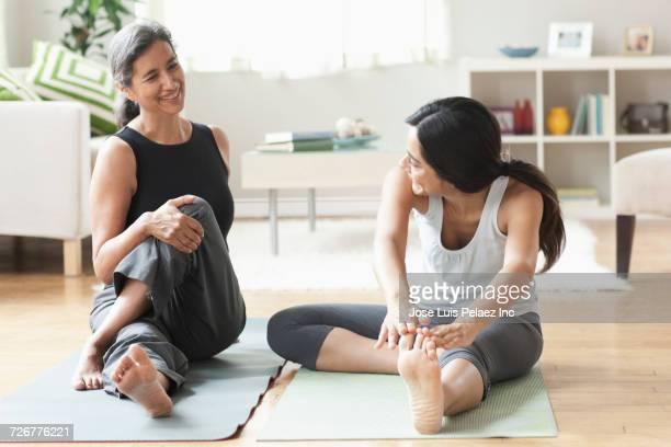 mother and daughter sitting on exercise mats and stretching legs - perna humana - fotografias e filmes do acervo