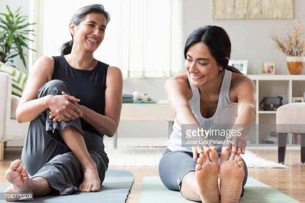 mother and daughter sitting on exercise mats and stretching - mujeres de mediana edad fotografías e imágenes de stock