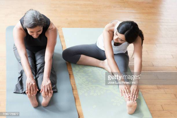 Mother and daughter sitting on exercise mats and stretching