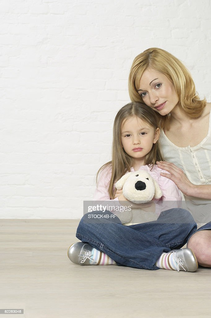 Mother and daughter sitting on floor : Stock Photo