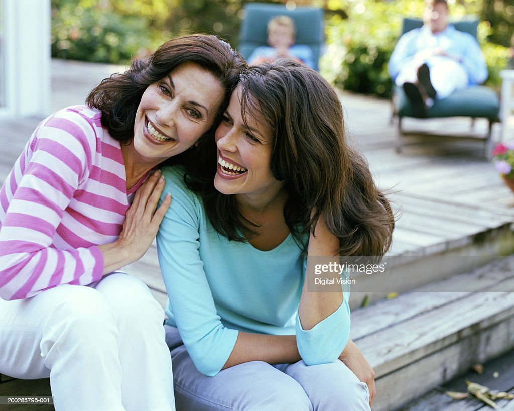 Mother and daughter sitting on garden deck, heads together, smiling : Stock Photo