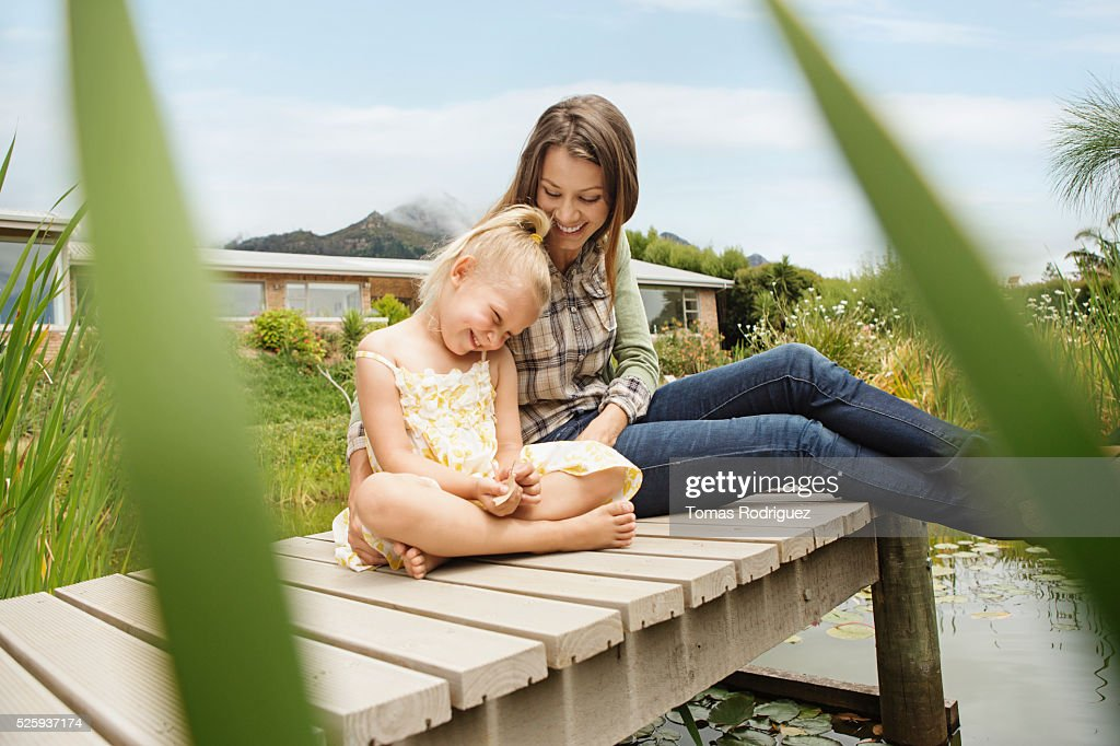 Mother and daughter (4-5) sitting on jetty : Foto stock