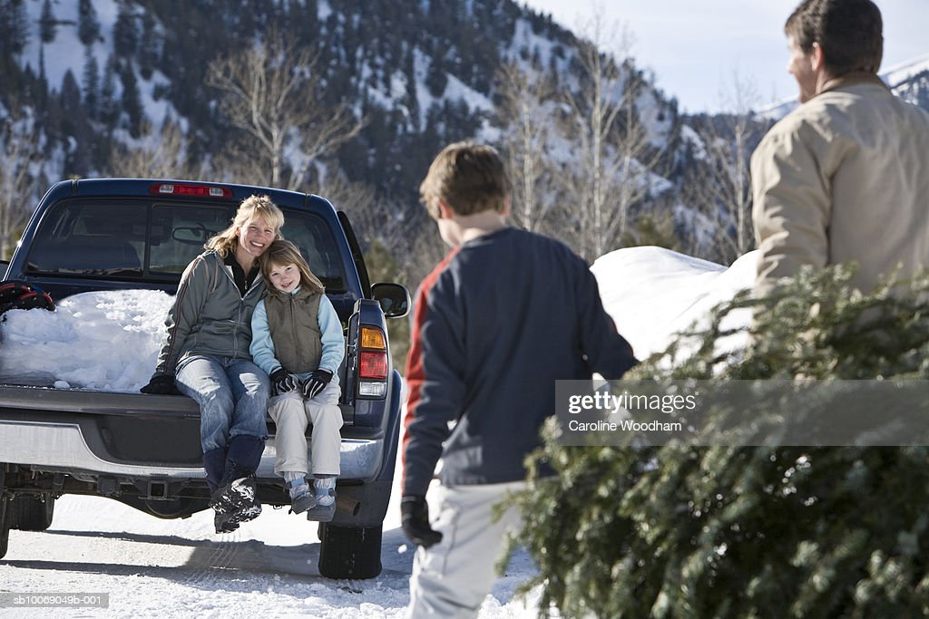 Mother and daughter (8-9) sitting on pick-up, father and son (10-11) carrying christmas tree : Stockfoto