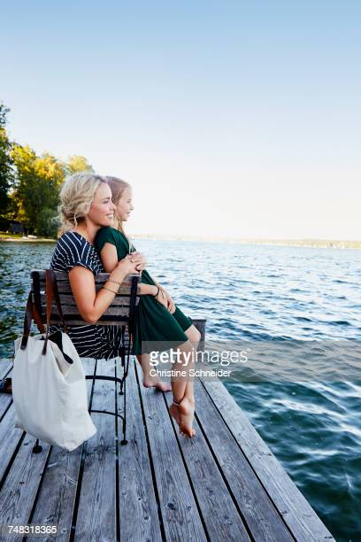 Mother and daughter sitting on pier by water