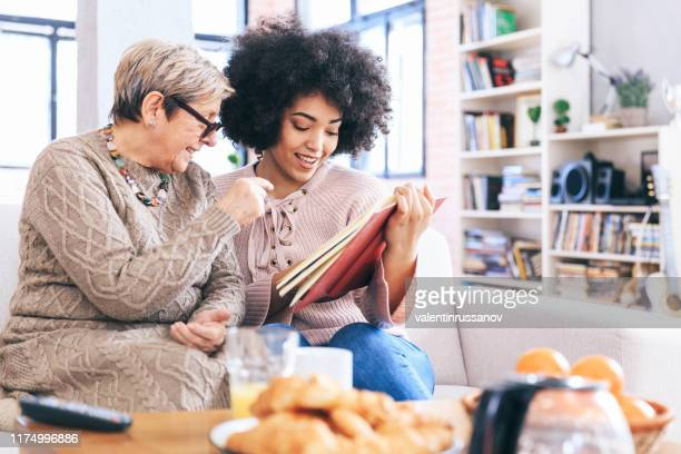 mother and daughter sitting on sofa at home - memories stock pictures, royalty-free photos & images