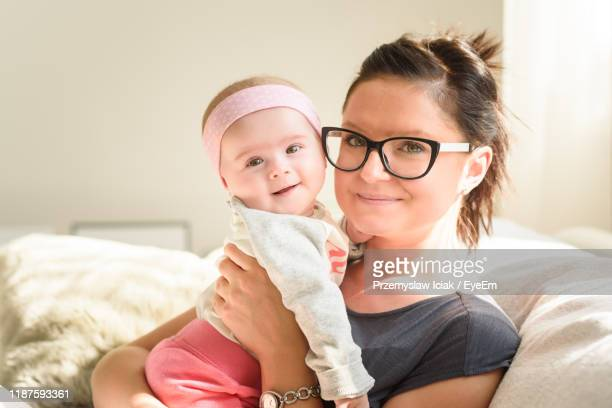 mother and daughter sitting on sofa at home - hazel bond stock photos and pictures