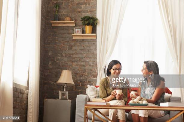 Mother and daughter sitting on sofa drinking tea and talking