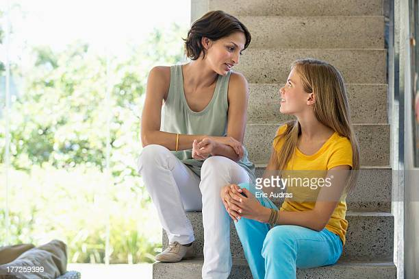 Mother and daughter sitting on steps and talking to each other