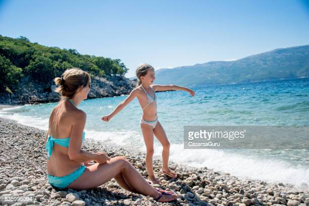 Mother And Daughter Sitting On The Sunny Beach Looking At View - Rear View