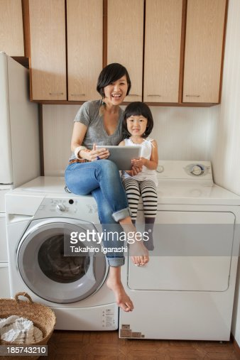 Mother And Daughter Sitting On Washing Machine Using