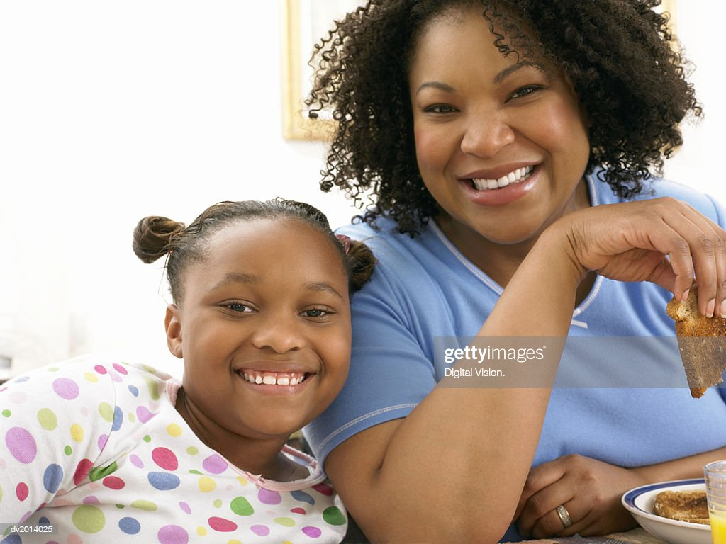 Mother and Daughter Sitting Side by Side at Breakfast : Stock Photo