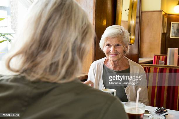 Mother and daughter sitting together in cafe