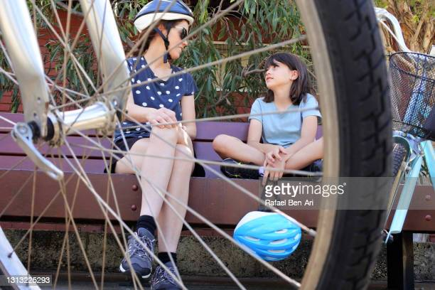 mother and daughter sitting together on a park bench having a conversation about bike riding - rafael ben ari ストックフォトと画像