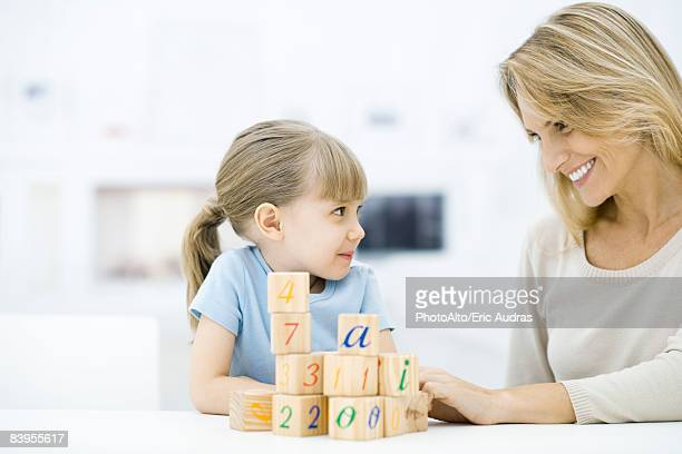 Mother and daughter sitting with blocks, smiling at each other