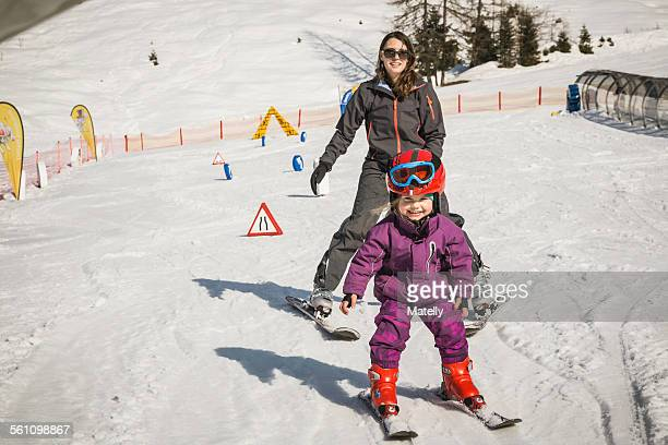 Mother and daughter skiing together, smiling