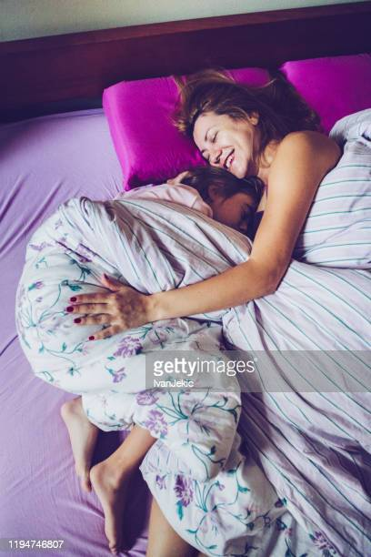 mother and daughter sleeping in bed - ivanjekic stock pictures, royalty-free photos & images