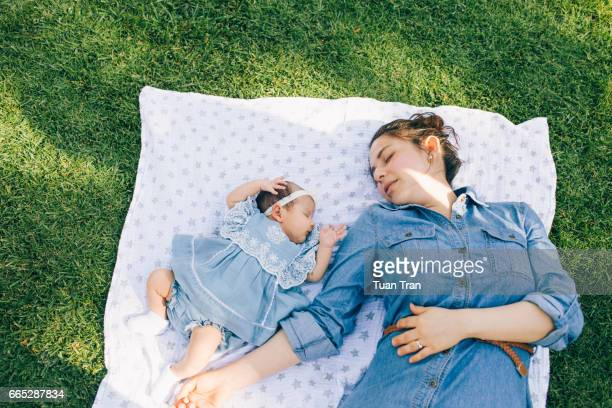 Mother and daughter sleeping in the grass