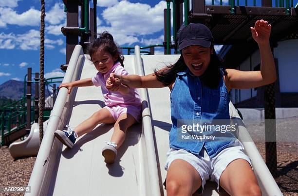 Mother and Daughter Sliding Down a Slide