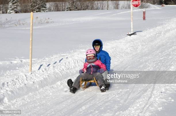 mother and daughter sliding down on an austrian toboggan during winter day - luge stock pictures, royalty-free photos & images