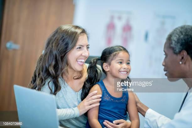 mãe e filha sorriam durante a consulta de um médico - pediatra - fotografias e filmes do acervo