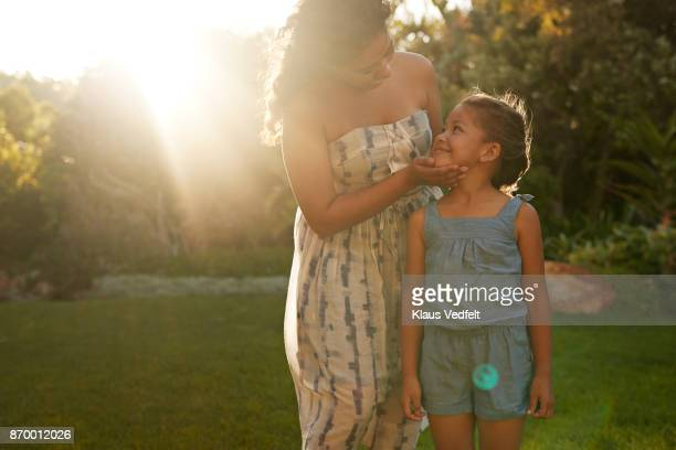 Mother and daughter smiling and looking at each other in garden