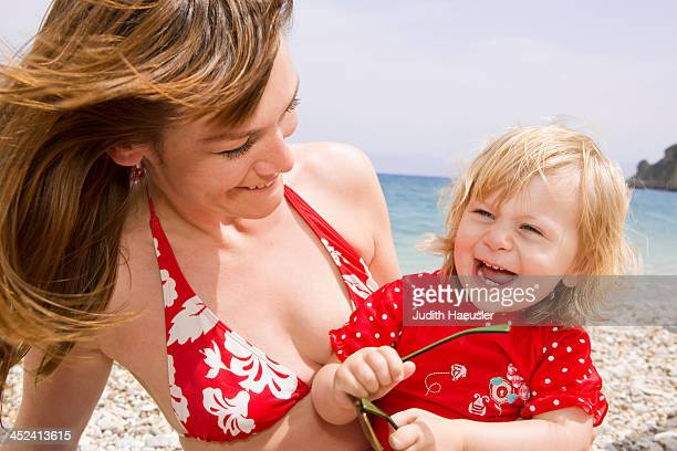 Mother and daughter smiling at beach