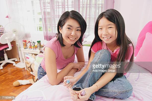 Mother and daughter smiling at camera, daughter painting toenails