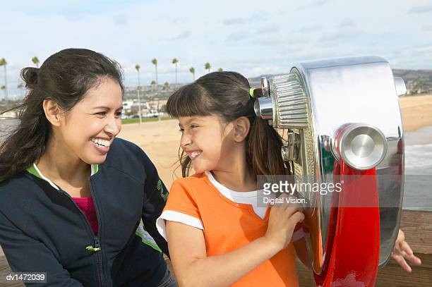 Mother and Daughter Smiling Face to Face Beside Coin-operated Binoculars