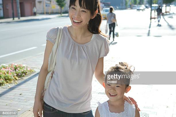 Mother and daughter smiling on street