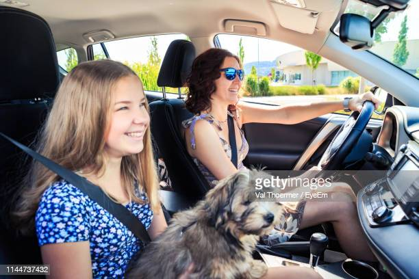 mother and daughter smiling sitting with dog in car - val thoermer stock-fotos und bilder