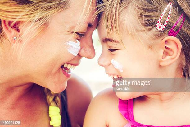 Mother and daughter smiling together with sunscreen on their cheeks