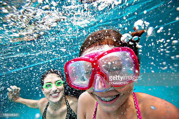 Mother and daughter smiling underwater in pool