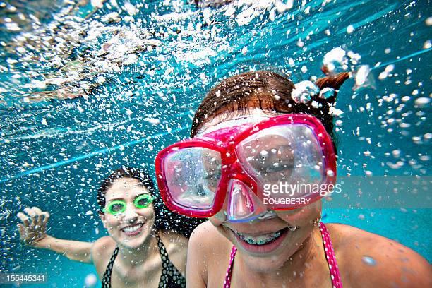 Mère et fille souriant sous l'eau dans la piscine
