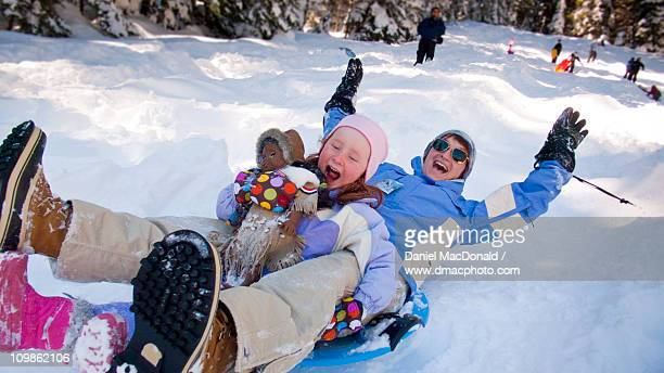 Mother and daughter snow sledding