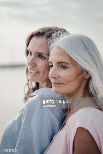 mother and daughter spending a day at the sea, portrait - vertikal stock-fotos und bilder