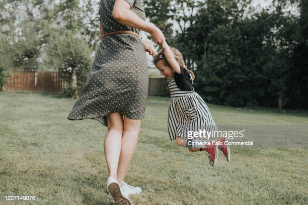 mother and daughter spinning - mother stock pictures, royalty-free photos & images