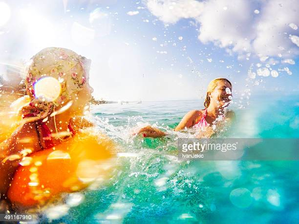 Mother and daughter splashing water in sea