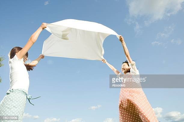 Mother and Daughter spreading white cloth up in air