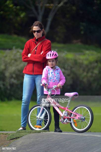 Mother and daughter stand and watch a bike race