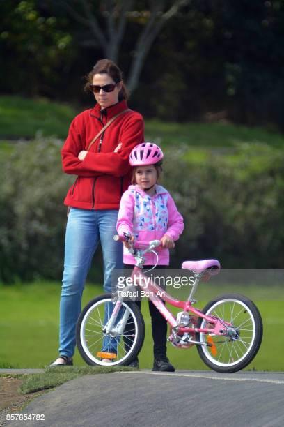 mother and daughter stand and watch a bike race - rafael ben ari stock-fotos und bilder