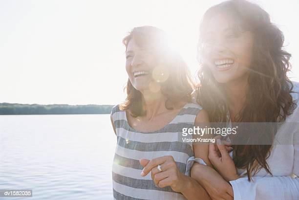 mother and daughter standing arm in arm at water's edge having fun - overexposed stock pictures, royalty-free photos & images