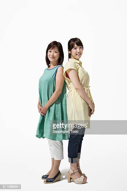 mother and daughter standing back to back - 背中合わせ ストックフォトと画像