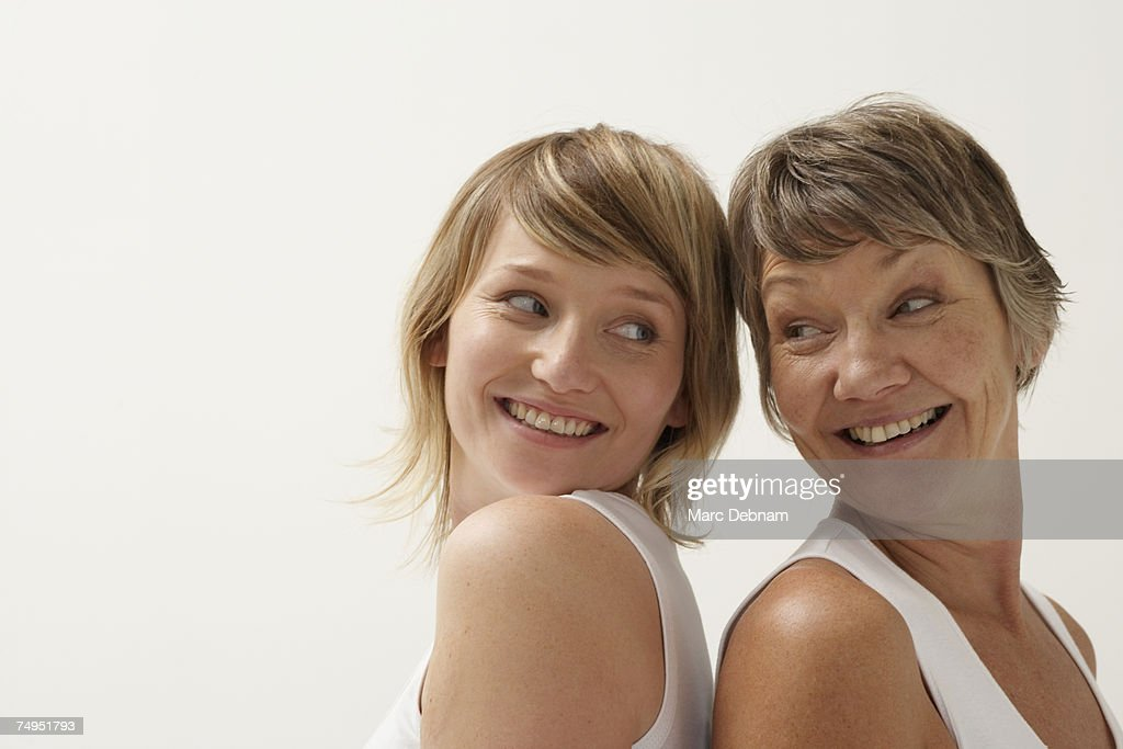 Mother and daughter standing back to back, smiling : Stock Photo