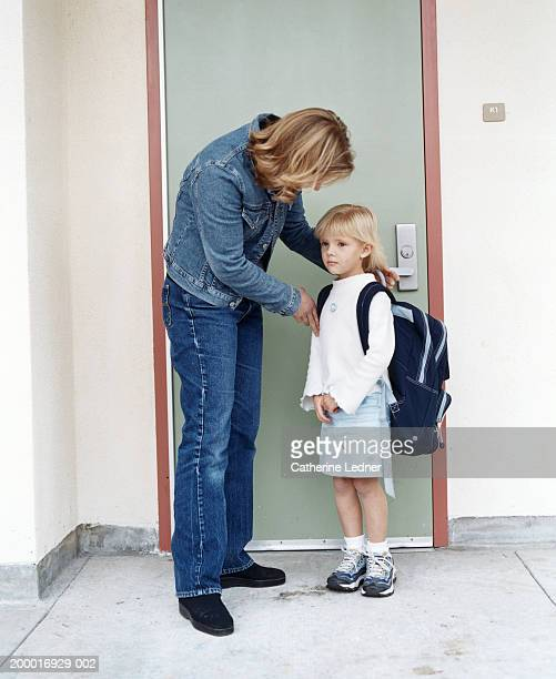 Mother and daughter (4-6) standing in front of classroom door