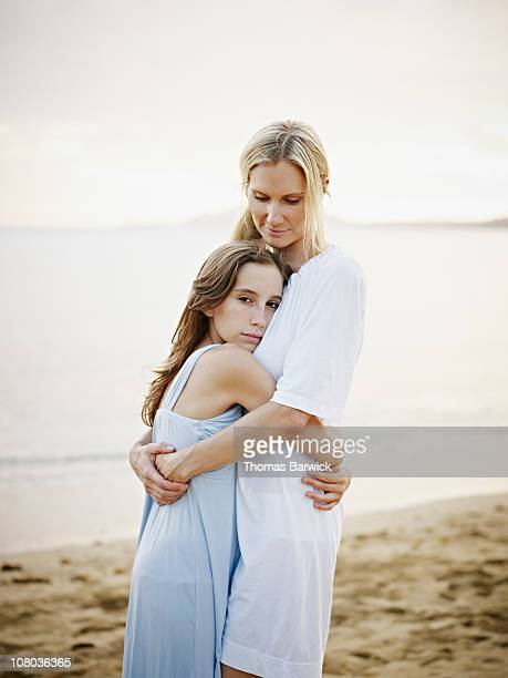 Mother and daughter standing on beach embracing