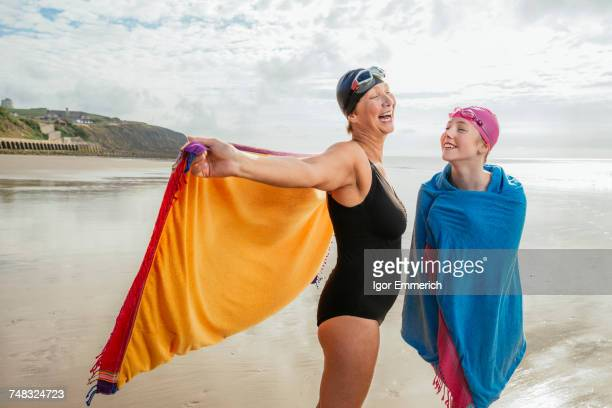 Mother and daughter standing on beach with shawls, Folkestone, UK