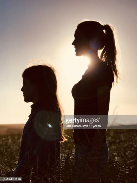 Mother And Daughter Standing On Field Against Clear Sky