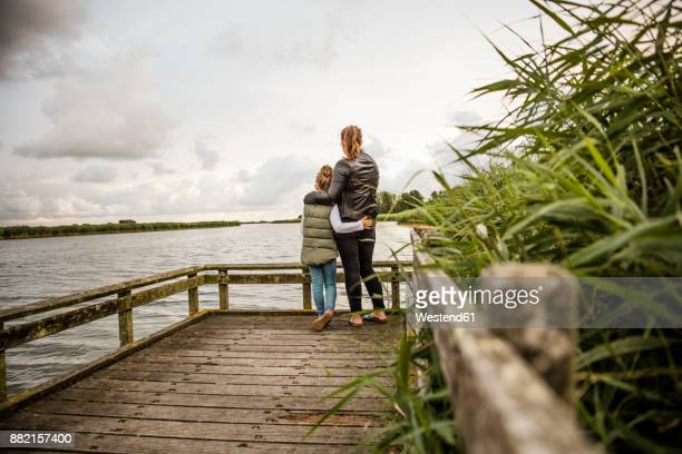 mother and daughter standing on jetty at a lake - friesland noord holland stockfoto's en -beelden